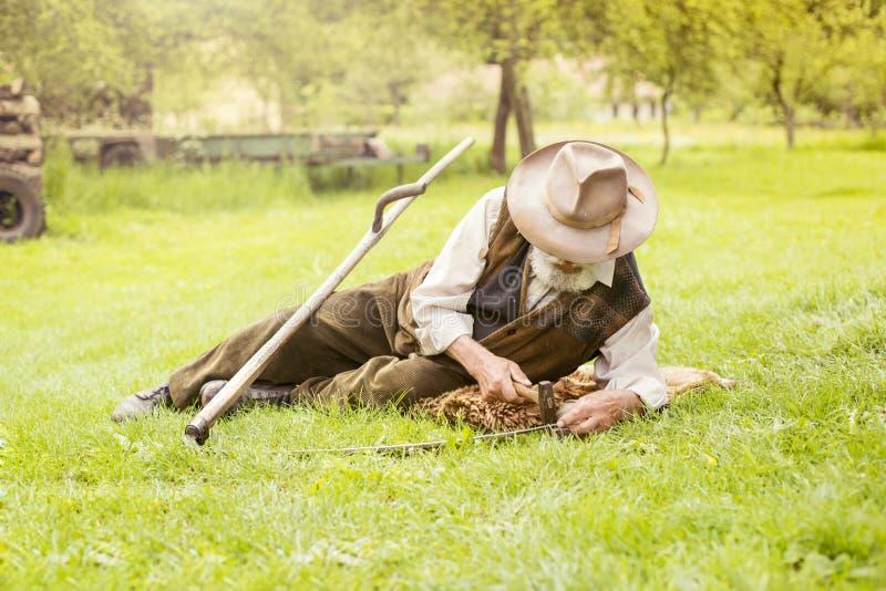 Старший фермер с косой стоковые фото