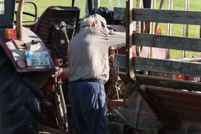 старший фермер haying с старым трактором стоковые фото