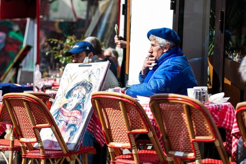 Старший художник при автопортрет сидя на кафе на известном Месте du Tertre в Montmartre стоковые фото