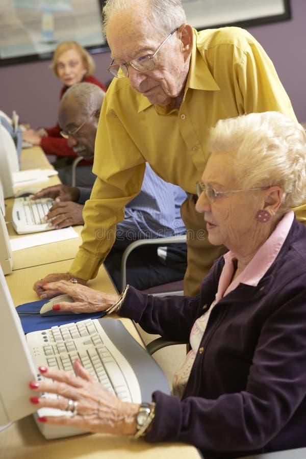 старший человека компьютера помогая для использования женщины стоковая фотография