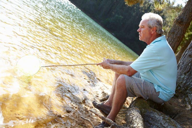 старший человека озера рыболовства стоковое фото
