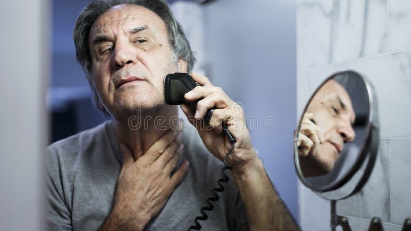 Старший человек брея его бороду в ванной комнате стоковое изображение rf