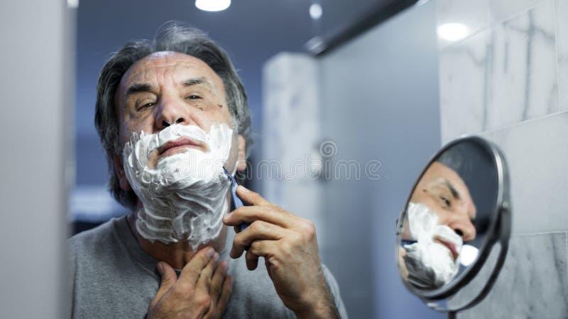 Старший человек брея его бороду в ванной комнате стоковые фото