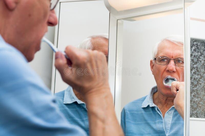 Старший человек в зеркале чистя его зубы щеткой стоковые фотографии rf