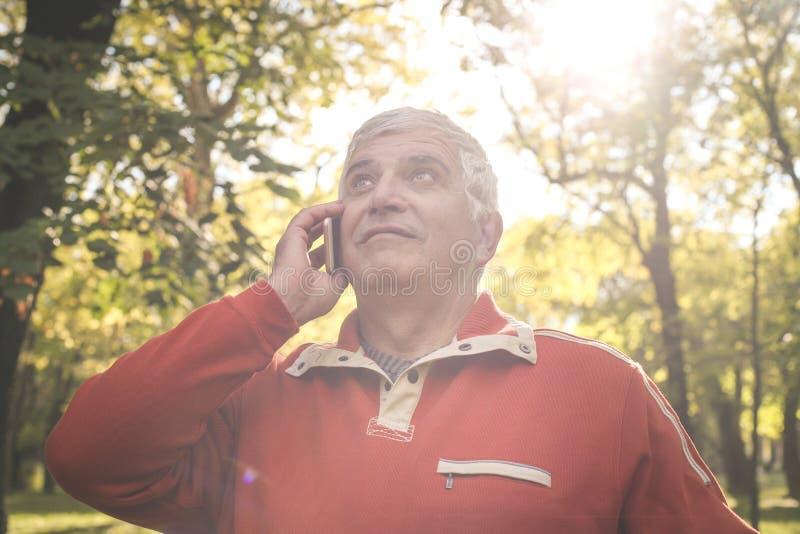 Старший человек в одежде спорт стоя в парке и talki стоковые фотографии rf