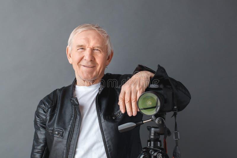 Старший человек в положении кожаной куртки изолированный на серый полагаться на камере на конце-вверх треноги усмехаясь шаловливо стоковая фотография rf