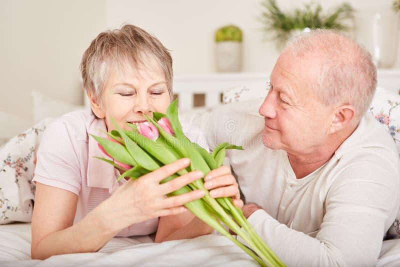 Старший человек дарит цветки стоковая фотография
