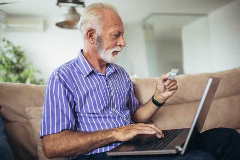 Старший человек делая онлайн ходить по магазинам дома стоковые фото