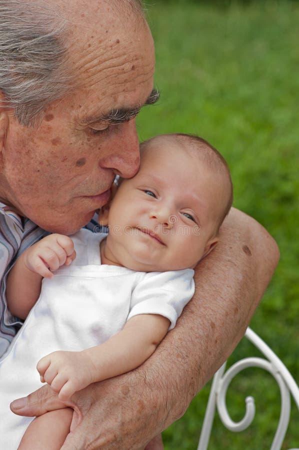 Старший человек держа его Great-grandson стоковое фото rf