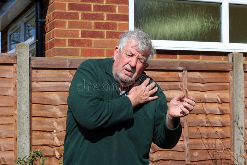 Старший человек держа тягостное плечо стоковая фотография