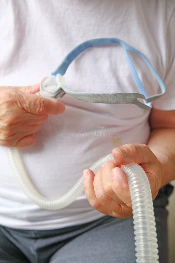 Старший человек держит прибор апноэ сна стоковая фотография