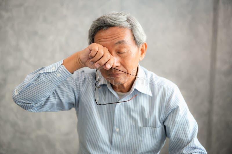 Старший человек держит eyeglasses и трет его утомленное whi глаз стоковое фото rf