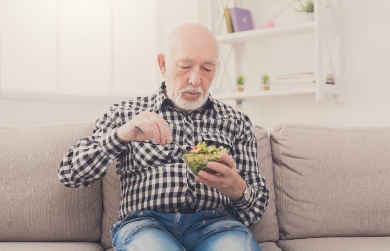 Старший человек есть свежий космос экземпляра салата стоковое фото