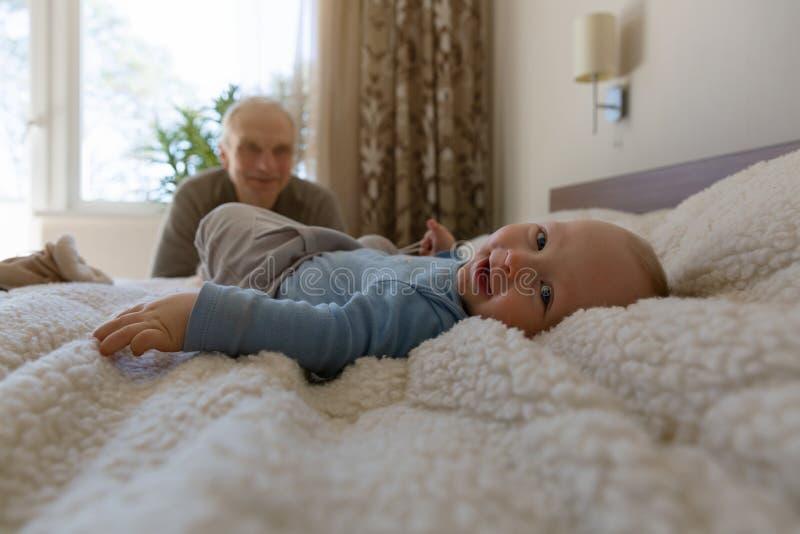 Старший человек играя с его внуком дома скрепляет болтами гайки семьи принципиальной схемы состава стоковое изображение rf