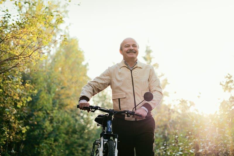 Старший человек идет для прогулки с велосипедом в сельской местности стоковое изображение rf