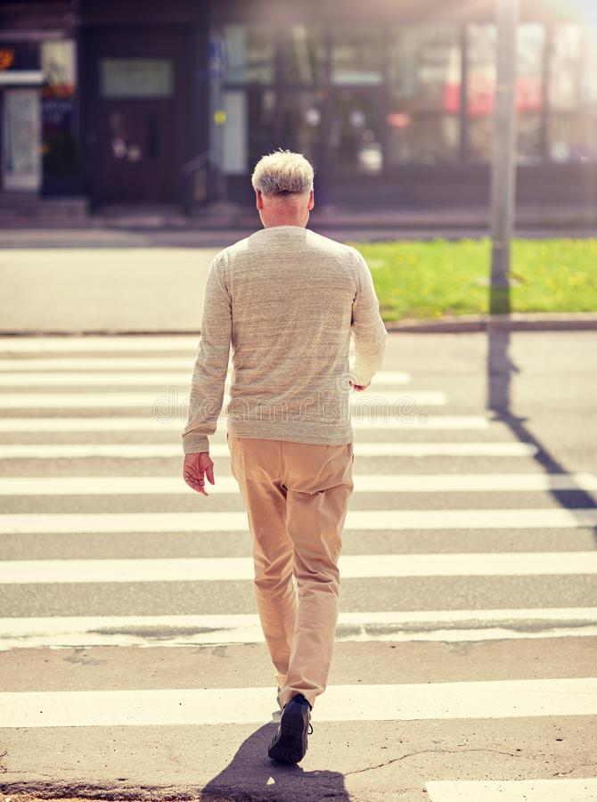 Старший человек идя вдоль crosswalk города стоковое изображение