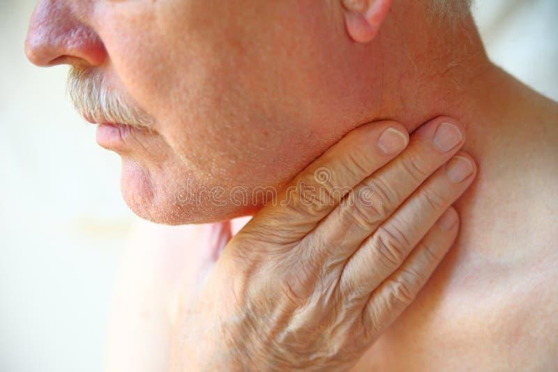 Старший человек имеет руку на горле стоковые фото