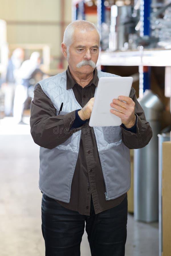 Старший человек используя цифровую таблетку в складе стоковые изображения