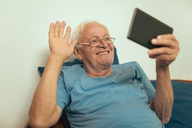 Старший человек используя цифровую таблетку стоковые изображения