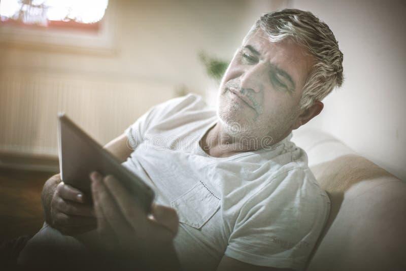 Старший человек используя цифровую таблетку стоковое фото rf