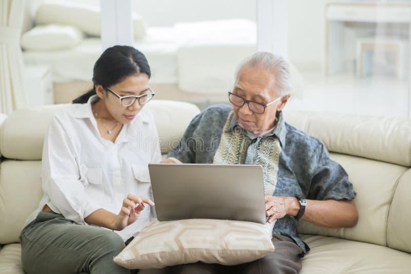 Старший человек и дочь используя ноутбук на софе стоковые фотографии rf