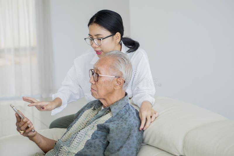 Старший человек и дочь используя смартфон на софе стоковая фотография
