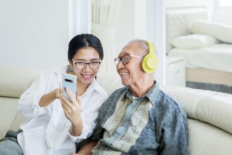 Старший человек и дочь наслаждаются музыкой на смартфоне стоковое фото