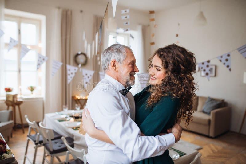 Старший человек и молодая женщина стоя внутри помещения в наборе комнаты для партии, обнимая стоковые изображения rf