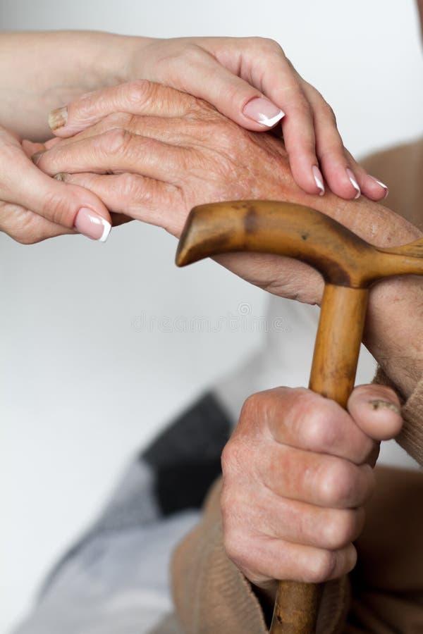 Старший человек и молодой попечитель держа руки на идя ручке, крупном плане стоковые изображения rf