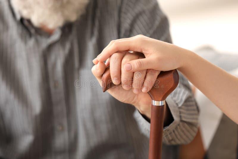 Старший человек и молодой попечитель держа руки стоковое фото