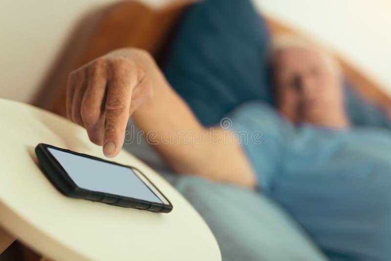 Старший человек поворачивает будильника сигнал тревоги на телефоне стоковые изображения rf