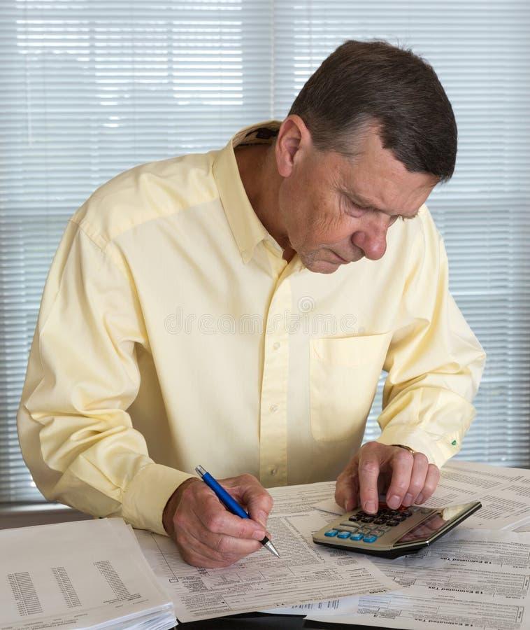 Старший человек подготовляя налоговую форму 1040 США на 2012 стоковые изображения