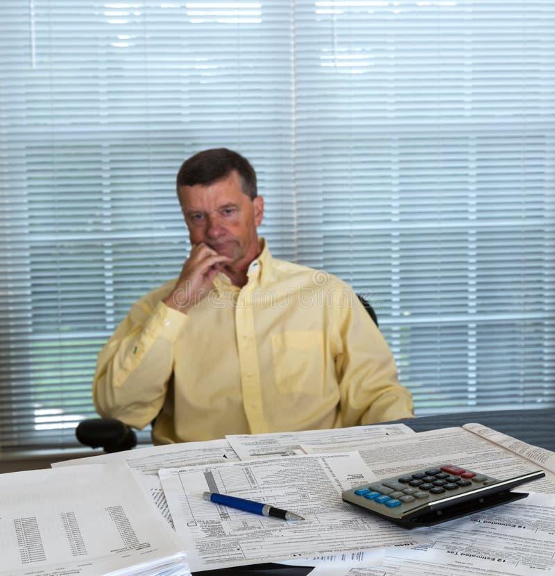 Старший человек подготовляя налоговую форму 1040 США на 2012 стоковые фото