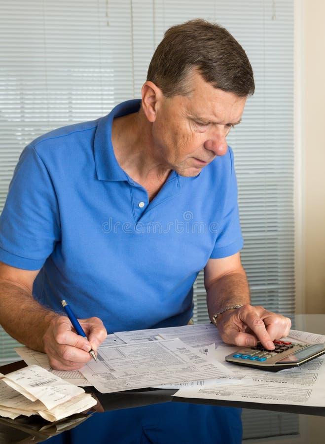 Старший человек подготовляя налоговую форму 1040 США на 2012 стоковое фото