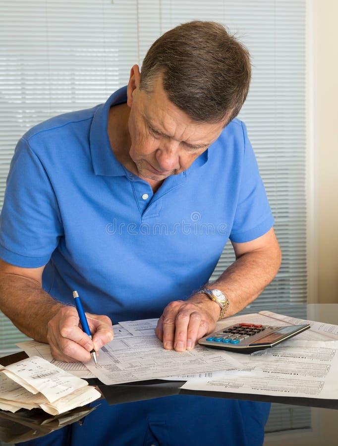 Старший человек подготовляя налоговую форму 1040 США на 2012 стоковое изображение