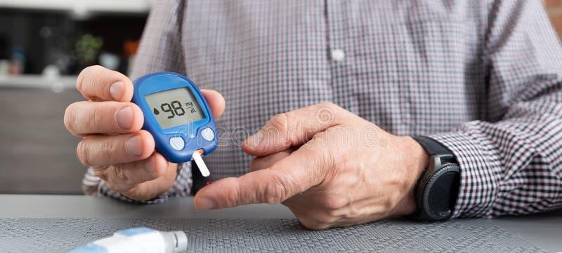 Старший человек проверяя уровень сахара в крови дома стоковые изображения rf