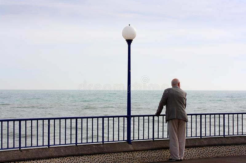 Старший человек смотря на море в прогулке Истборна в Сассекс стоковые фотографии rf