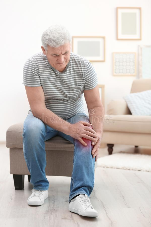 Старший человек страдая от боли колена стоковая фотография rf