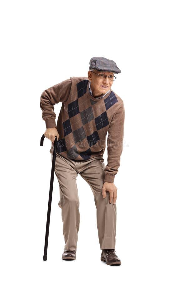 Старший человек с болью колена идя с тросточкой стоковые изображения rf