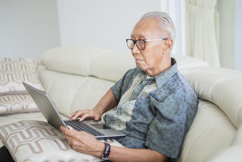 Старший человек с серыми волосами используя ноутбук стоковое изображение rf
