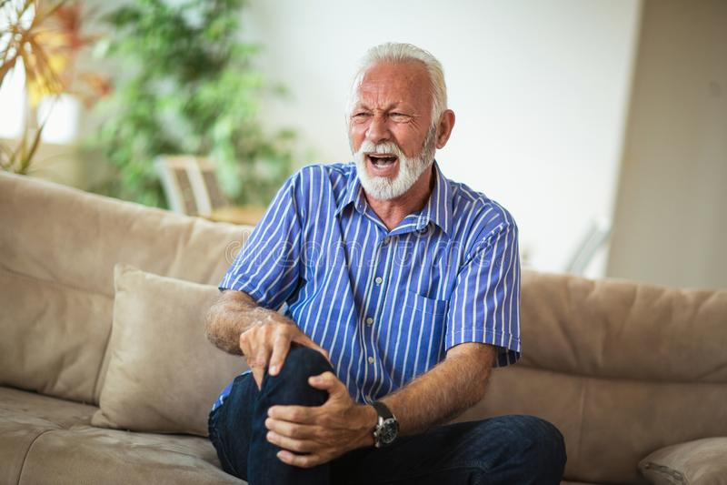 Старший человек с хроническими проблемами колена стоковые изображения rf