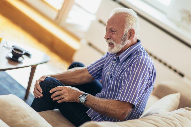 Старший человек с хроническими проблемами колена стоковое изображение rf