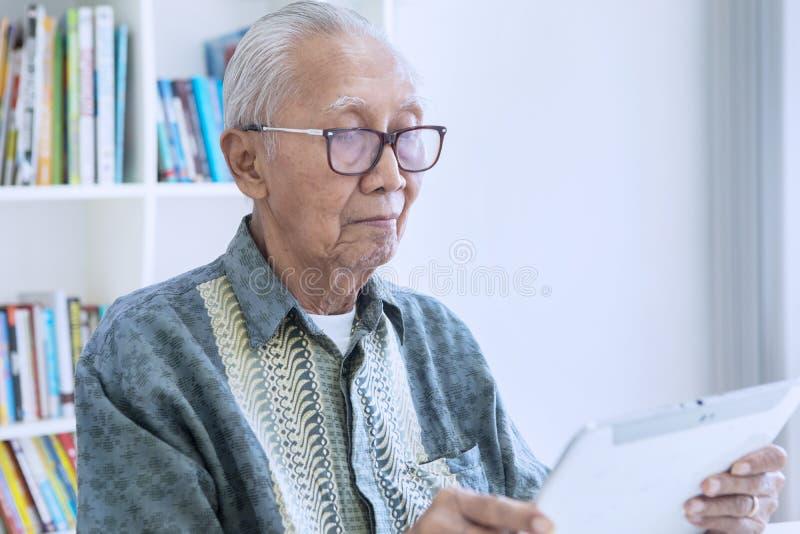 Старший человек с цифровым планшетом в библиотеке стоковое изображение rf