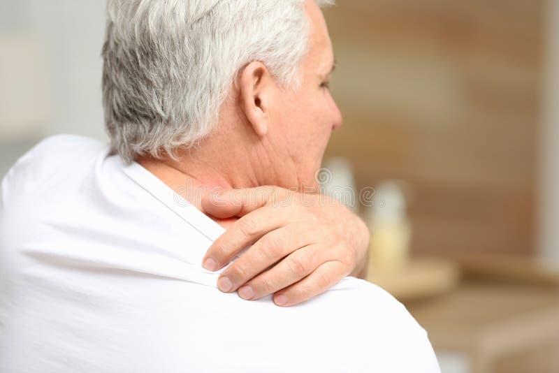 Старший человек царапая плечо внутри помещения, крупный план Симптом аллергии стоковое изображение rf
