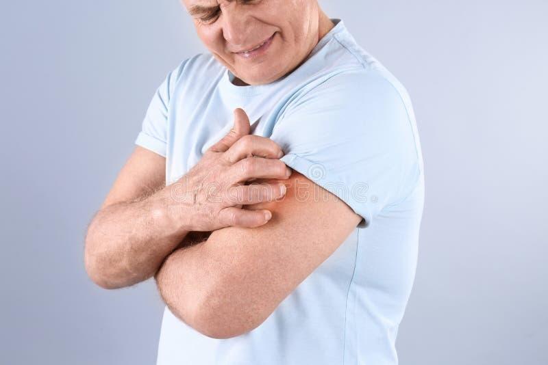 Старший человек царапая руку на серой предпосылке Симптом аллергии стоковое изображение