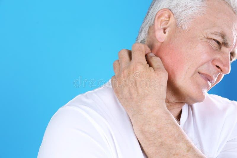 Старший человек царапая шею на предпосылке цвета Симптом аллергии стоковые изображения rf
