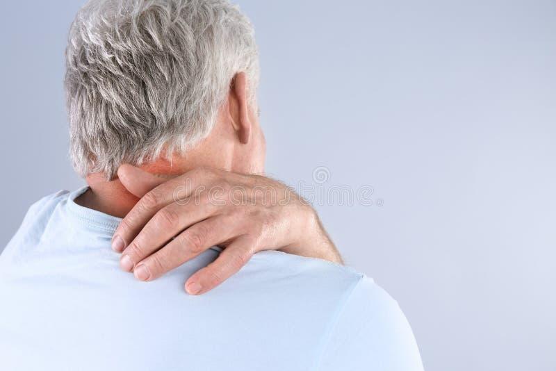 Старший человек царапая шею на серой предпосылке Симптом аллергии стоковые изображения rf