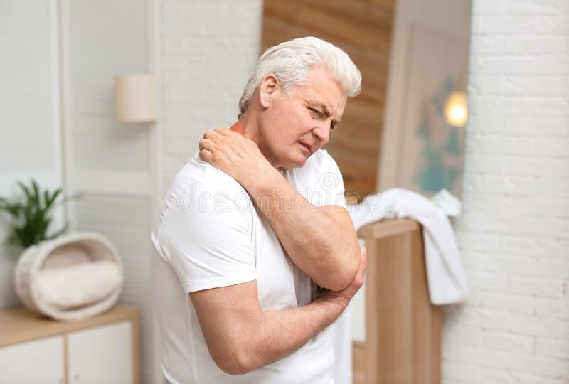 Старший человек царапая шею Симптом аллергии стоковое фото rf
