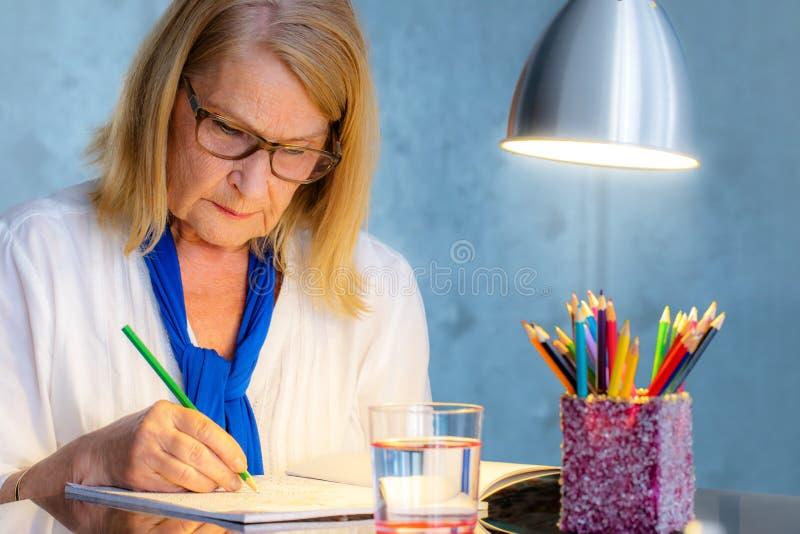 Старший чертеж женщины в книге цвета для взрослых стоковое фото