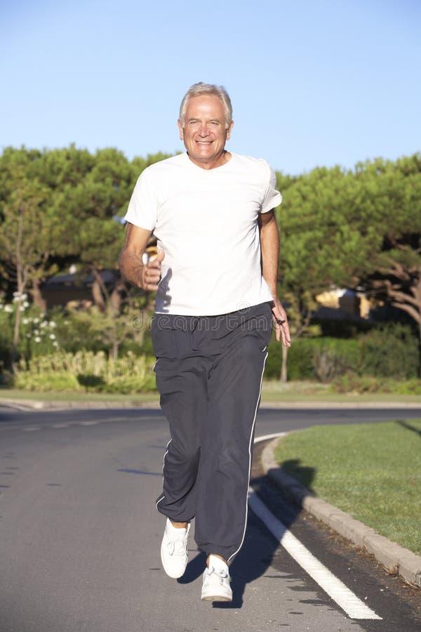 Старший человек бежать на дороге стоковые изображения